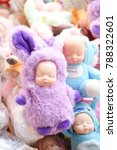 Small photo of Cute newborn baby doll in purple fluffy bunny suit, plaything for little children. soft focus on the right eye