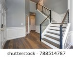 Luxury custom built home interior. Stunning two story entrance foyer design with white wainscoting, grey walls and a staircase.