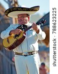 Small photo of Puerto Vallarta, Jalisco / Mexico - 10/01/2016: Mariachi Plays a Vihuela for Beach Audience Wearing Traditional White Suit, Charro Shirt, Sombrero Hat and Mexican Tie.