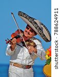 Small photo of Puerto Vallarta, Jalisco / Mexico - 10/01/2016: Mariachi Plays a Violin for Beach Audience Wearing Traditional White Suit, Charro Shirt, Sombrero Hat and Mexican Bow Tie.
