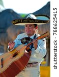 Small photo of Puerto Vallarta, Jalisco / Mexico - 10/01/2016: Mariachi Plays a Guitarron for Beach Audience Wearing Traditional White Suit, Charro Shirt, Sombrero Hat and Mexican Bow Tie.
