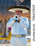 Small photo of Puerto Vallarta, Jalisco / Mexico - 10/01/2016: Mariachi Plays a Silver Trumpet for Beach Audience Wearing Traditional White Suit, Charro Shirt, Sombrero Hat and Mexican Bow Tie.