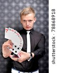 magician shows stunts and tricks with cards, sleight of hand ,glamour background - stock photo