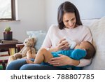 mother holding and feeding baby ... | Shutterstock . vector #788807785