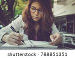 Small photo of young woman concentrate reading book. girl learning writing homework. education assessment concept. Student studying college exam, doing homework at university. concentration on admissions in college.