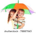 Two little children under colored umbrella - stock photo