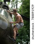 Small photo of Goal, achievement, success. Man climb on helicopter in forest. Travelling, discovery, adventure. Sportsman with muscle body on heli aircraft. Ambition, dream, priority concept.