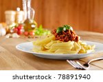 Penne pasta with a tomato bolognese beef sauce on the kitchen table - stock photo