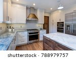 Stock photo luxury home interior boasts amazing kitchen with custom white shaker cabinets endless marble 788979757