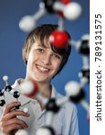 Small photo of Kids and Science, Teenage Boy looking at a Model of Molecules in Amazement on Blue Background