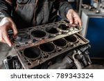 Small photo of Sealing gasket in hand. The mechanic disassemble block engine vehicle. Engine on a repair stand with piston and connecting rod of automotive technology. Interior of a car repair shop.