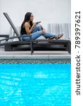 Small photo of Black female on a speaker phone call in a hotel resort. She is working while on vacation or dictating reminders on a voice assistant on her cellphone.