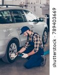 Small photo of Bearded specialist, technician expert in protective glasses, blue overall, checkered shirt is analyzing tire physical pressure of silver car on hardware in workstation