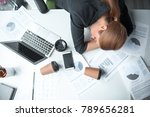 Small photo of Top view serene weary female lying on desk in modern office. Mugs of beverage and different documents locating on it. Job and fatigue concept