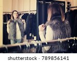 young woman trying on fur vest... | Shutterstock . vector #789856141