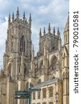 Small photo of York Minster towering above with a signpost at its foot. A cloudy sky is aloft.