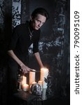 Small photo of thin dark goth sorcerer performs a night ritual on black background