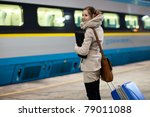 Train is coming - young woman waiting for her connection in a modern train station (shallow DOF) - stock photo