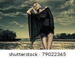 blond fashion model on beach with poncho. - stock photo