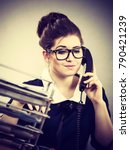 Small photo of Business woman sitting working at desk full off documents in binders talking with someone on phone