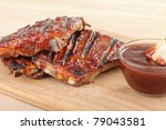 Grilled barbecue spareribs and barbecue sauce on a cutting board - stock photo