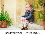 Adorable little girl outdoors sitting near door and old yellow wall - stock photo