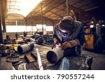 Small photo of Close up portrait view of professional mask protected welder man working on the metal sculpture in the industrial fabric workshop in front of few other workers.