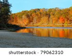 Brilliant autumn colors reflected in a serene lake (Punderson Lake in northeast Ohio) - stock photo