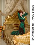 Small photo of Young beautiful fashion model on lux bedroom with passion. Beautiful woman in velvet bathrobe. Home luxurious golden interior