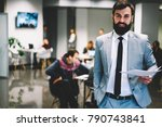 Small photo of Portrait of successful entrepreneur coacher dressed in stylish suit looking at camera while standing with paper documents in hands with office employees on blurred background