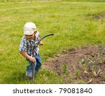 Little boy playing with garden hose - stock photo