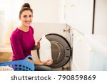 Small photo of Portrait of the young cheerful woman who sitting near washing machine in the room and holding abstergent in hand