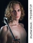 Small photo of Young valiant knight looking man with rich blond curls holding a steel mace, black background
