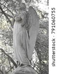 Small photo of Sad angel as a symbol of eternity, life, death and afterlife. Vintage image of a sad angel in a cemetery. Angel and guardian.