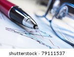 Business performance graph with ballpoint pen and glasses - stock photo