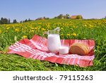 Jug of milk and bread on the spring meadow. Emmental region, Switzerland - stock photo