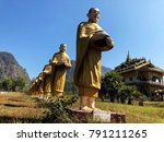 Small photo of Statue of monks holding alms bowl and Standing as a wall with Beautiful sky background, The wall of the temple is made of a monk holding alms bowl. Religion of Buddhist