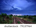 Rural road and dark storm clouds - stock photo