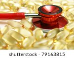 A macro shot of a stethoscope and Omega-3 supplements to address the benefits of their intake for a healthy heart. - stock photo