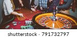 People play poker roulette at the table. Friends playing in the casino. A group of young people at a roulette table with a tape measure. Gambling. Vintage photo processing / black and white photo - stock photo