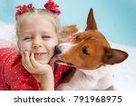Stock photo little blonde curly girl hugging a red basenji dog a dog licks a girl s cheek 791968975