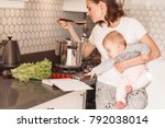 Woman Cooking With Her Little...