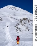 Small photo of Climbing lone alpinist in the Caucasus mountains Elbrus, climb up the trail snowcat