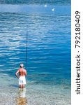 Small photo of Arona, Italy - May 23, 2012: A senior fishermen in white knickers on the Maggiore lake