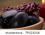 hot massage stone in a bowl with potpourri - stock photo