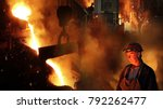 Small photo of Hard work in foundry, liquid metal in the foundry, melting iron in furnace, steel mill. Workers controlling iron smelting in furnaces
