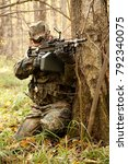 Small photo of October 2009. Moscow Region, Russia - an airsoft player wearing german camouflage flecktarn aims at an enemy with m249 machin gun replica during a game