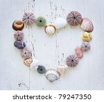 Heart made of Mediterranean sea shells, urchins and rocks on painted wood - stock photo
