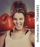 Small photo of Sporty having head between boxing gloves, somebody punching her. Studio shot on grey background.