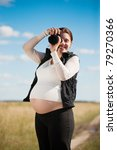 pregnant woman with camera against summer field - stock photo